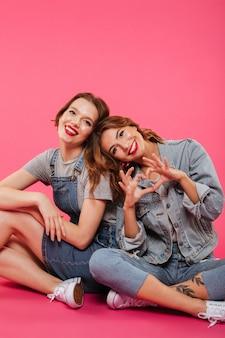 Dos amigas felices sentados en el piso mostrando el gesto del corazón.