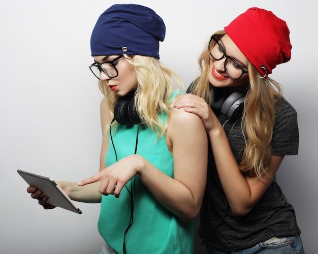 Dos amigas hipster usan tableta digital