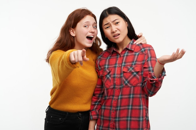 Dos amigas jóvenes. chica mostrando algo a su amiga, pero otra no puede ver. vistiendo suéter amarillo y camisa a cuadros. aislado sobre pared blanca