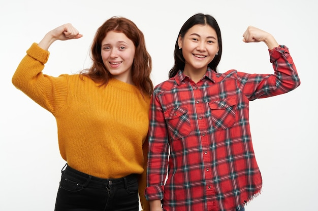 Dos amigas jóvenes y felices. vistiendo suéter amarillo y camisa a cuadros. mostrando lo fuertes que son, músculos. llena de energía. concepto de personas. aislado sobre pared blanca