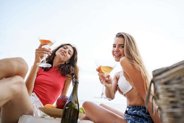 Dos amigas jóvenes haciendo un picnic en la playa bebiendo cócteles