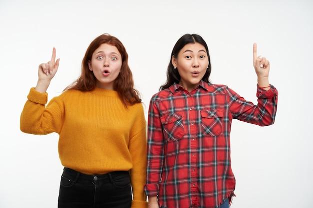 Dos amigas jóvenes sorprendidas. vistiendo suéter amarillo y camisa a cuadros. concepto de personas. mirando asombrado y apuntando hacia arriba en el espacio de la copia, aislado sobre la pared blanca