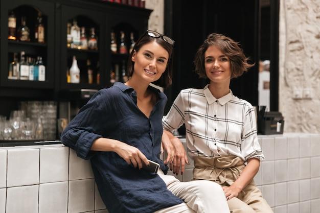 Dos amigas muy sonrientes sentadas ordenadas en el bar