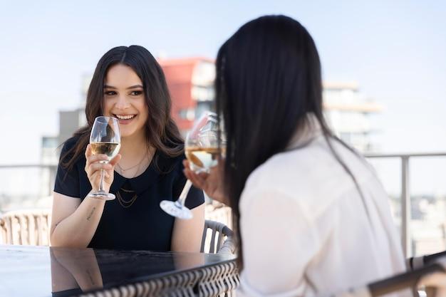 Dos amigas pasar tiempo juntos y beber vino en una terraza en la azotea