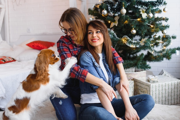 Dos amigas con perro están sentadas en el suelo sonriendo en una habitación luminosa en el fondo de un árbol de navidad