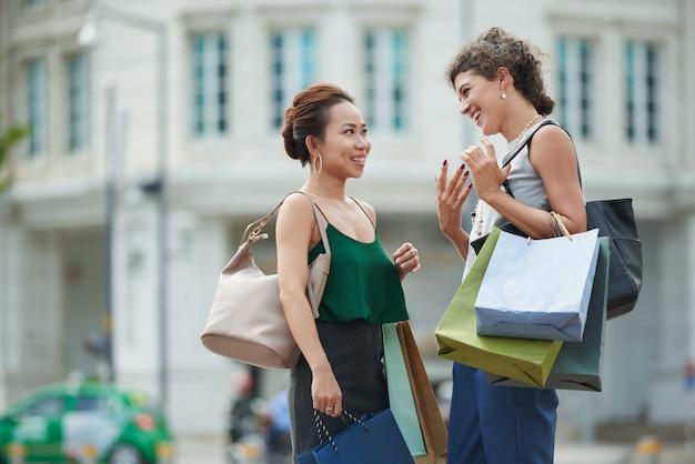 Dos amigas de pie en la calle con bolsas de compras y charlando