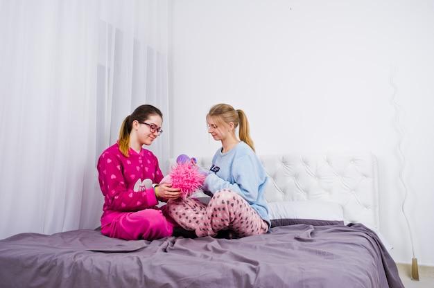 Dos amigas en pijama divirtiéndose en la cama en la habitación.