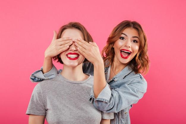 Dos amigas que cubren los ojos con las manos.
