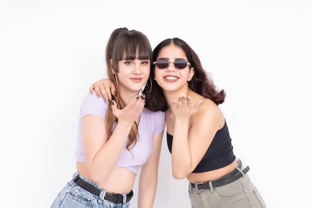 Dos amigas que soplan un beso a la cámara divirtiéndose en blanco
