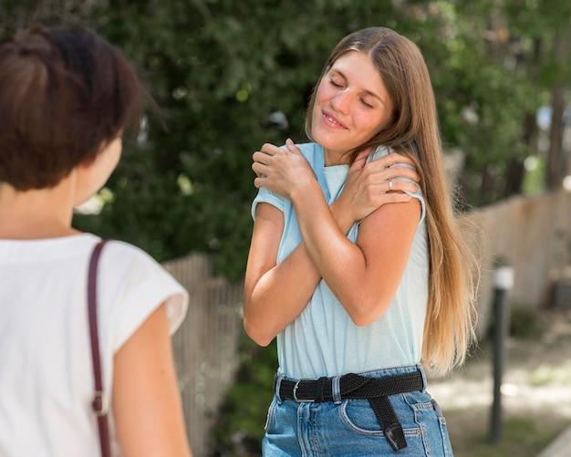 Dos amigas que utilizan el lenguaje de señas para conversar entre sí