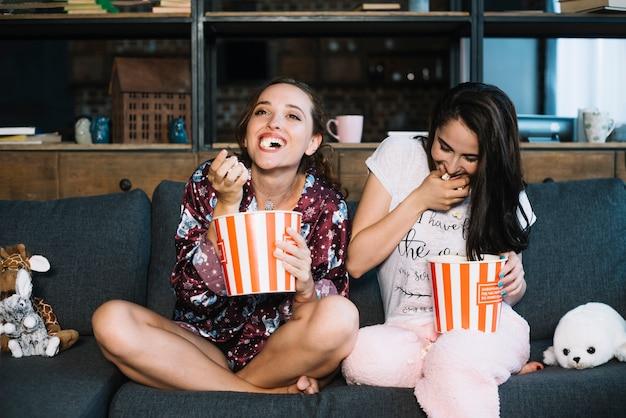 Dos amigas riendo mientras ve la televisión