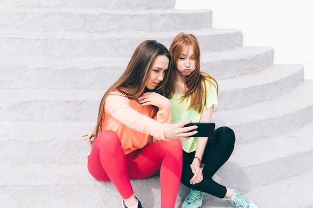 Dos amigas en ropa deportiva se toman fotos en un teléfono móvil y se ríen.