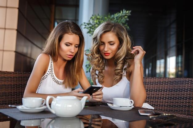 Dos amigas sentadas en la cafetería