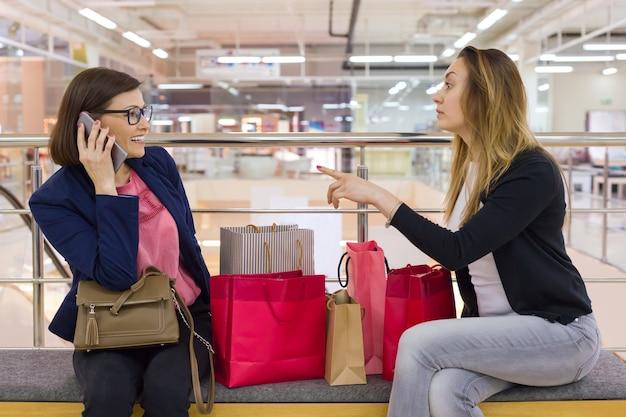 Dos amigas sentadas en el centro comercial después de ir de compras, mirando bolsas, descansando.