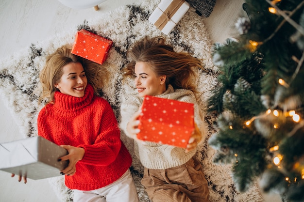 Dos amigas sentadas con regalos de navidad junto al árbol