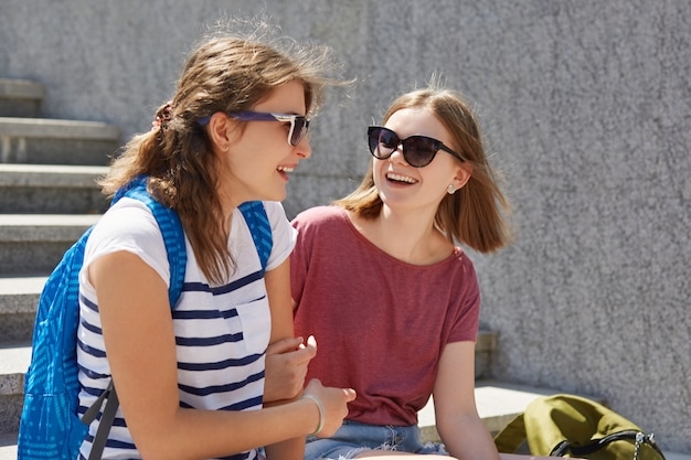Dos amigas se sientan en pasos al aire libre