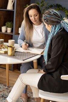 Dos amigas socios de la red de negocios de venta de productos cosméticos navegando por internet usan laptop