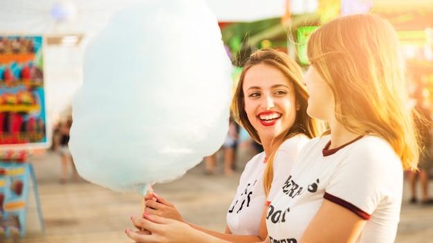 Dos amigas sonrientes con hilo de caramelo azul