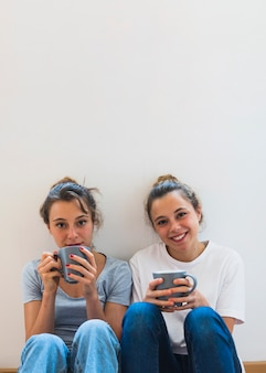 Dos amigas sosteniendo la taza de café sentado contra el telón de fondo blanco