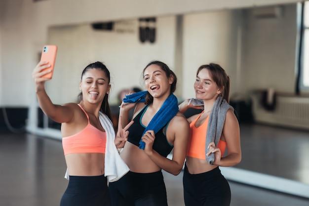 Dos amigas tomando una foto selfie después de un duro entrenamiento en el gimnasio.