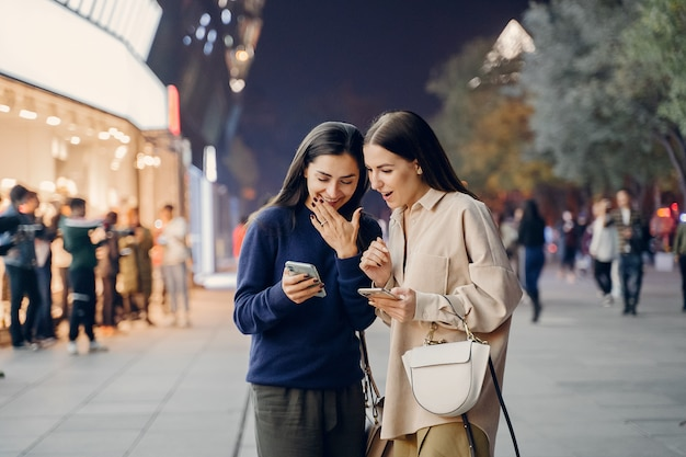 Dos amigas usando su teléfono celular mientras exploran una nueva ciudad por la noche