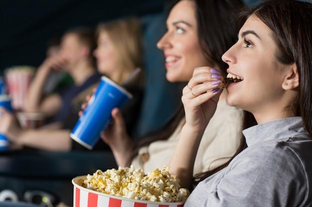 Dos amigas viendo una película en el cine juntas.