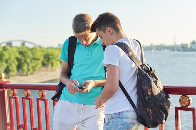 Dos amigos adolescentes usando teléfono inteligente, hablando y sonriendo