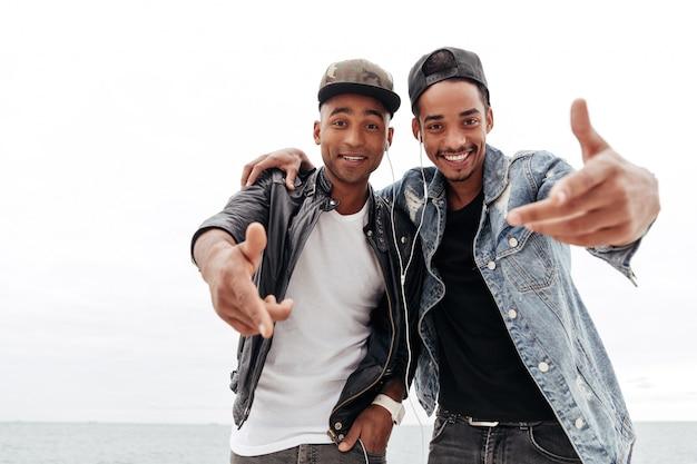 Dos amigos africanos jóvenes felices escuchando música.
