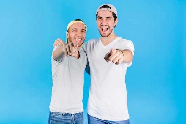 Dos amigos alegres apuntando a la cámara