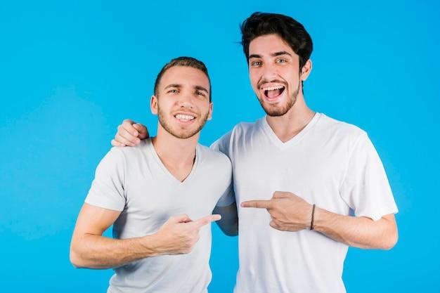 Dos amigos alegres apuntándose el uno al otro