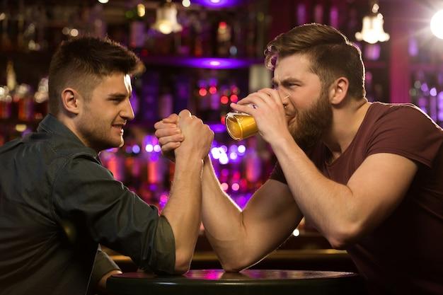Dos amigos bebiendo cerveza y divirtiéndose en el pub
