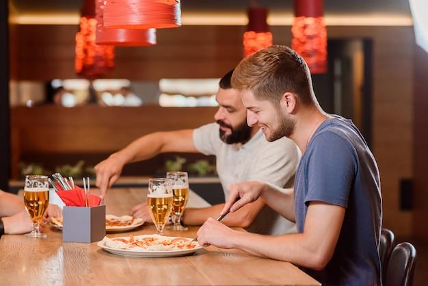 Dos amigos comiendo pizza con cuchillo y tenedor.