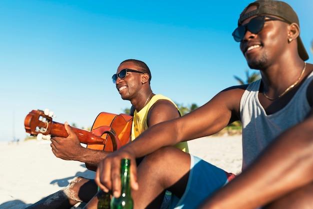 Dos amigos cubanos divirtiéndose en la playa con su guitarra. concepto de amistad.