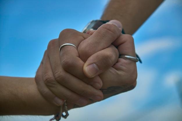 Dos amigos dándose la mano, detalle de manos entrelazadas en símbolo de ayuda, hermandad, amistad y respeto.