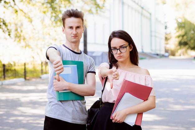 Dos amigos enojados y desconcertados que sostienen libros, notas y otros materiales de aprendizaje señalando con el pulgar hacia abajo en la calle cerca de la antigua universidad convencional