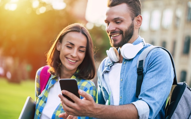 Dos amigos estudiantes felices y emocionados con mochilas y teléfonos inteligentes conversan y caminan al aire libre. hermosa pareja después de lecciones en la universidad