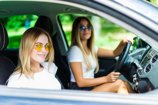 Dos amigos felices en el automóvil conducen por todas partes y buscan libertad y diversión