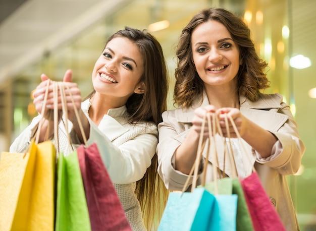 Dos amigos felices están de compras en el centro comercial y mirando a la cámara.