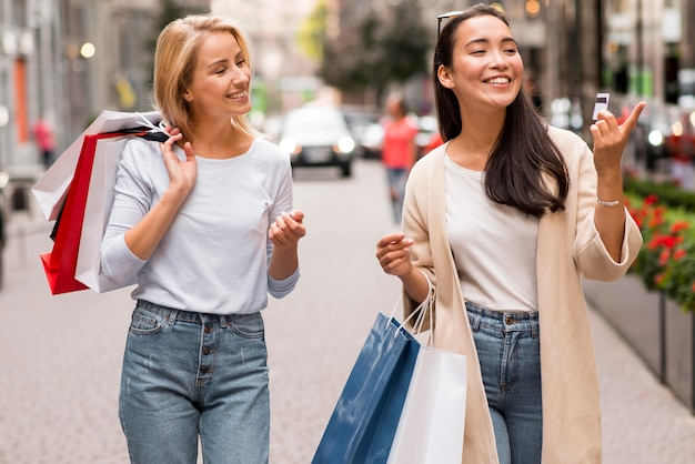Dos amigos felices para una sesión de compras con bolsas de la compra.