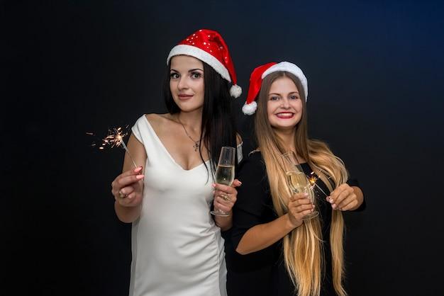 Dos amigos con fuegos de bengala y champán celebrando el año nuevo