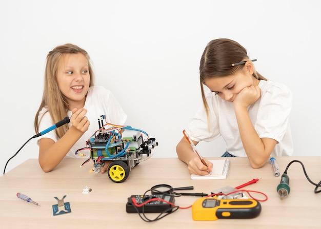 Dos amigos haciendo experimentos científicos con coche robótico.