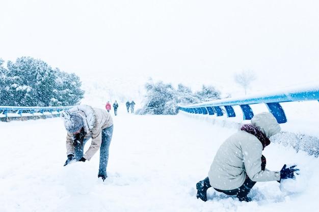 Dos amigos haciendo un muñeco de nieve
