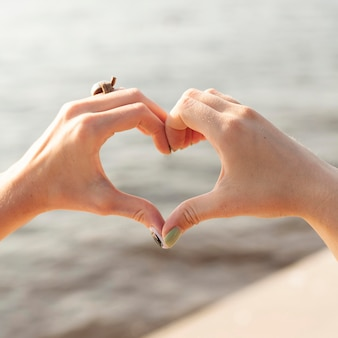 Dos amigos haciendo el signo del corazón en el lago con las manos
