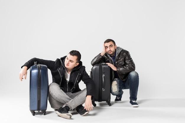 Dos amigos hombres casuales sentados en el suelo con equipaje esperando vuelo retrasado aislado sobre fondo blanco.