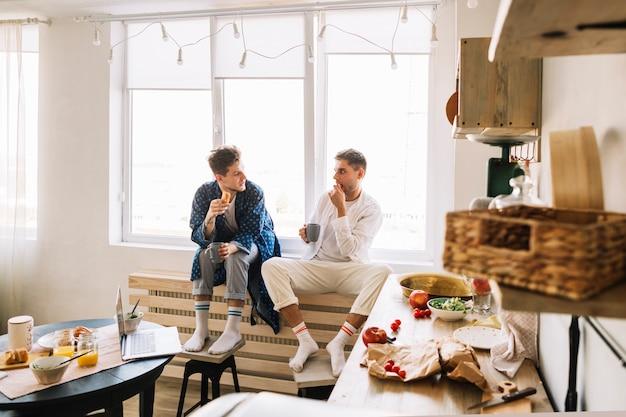 Dos amigos hombres sentados en la cocina desayunando