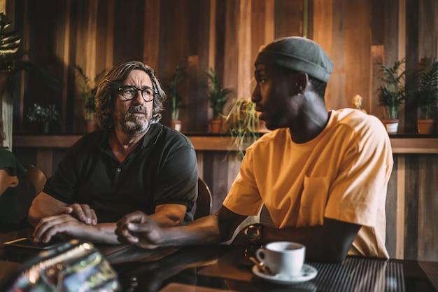 Dos amigos interraciales cenando y hablando en un restaurante