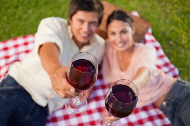 Dos amigos levantando sus copas de vino durante un picnic