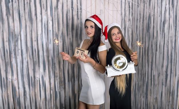 Dos amigos con luces de bengala y reloj en estudio