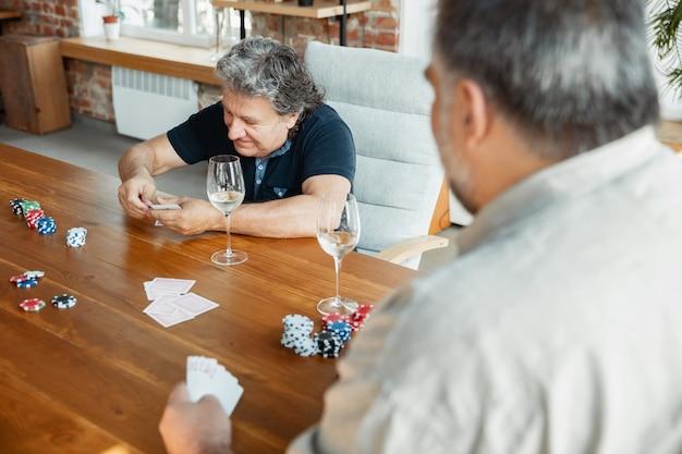 Dos amigos maduros felices jugando a las cartas y bebiendo vino