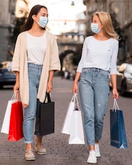 Dos amigos con máscaras médicas para una juerga de compras de venta